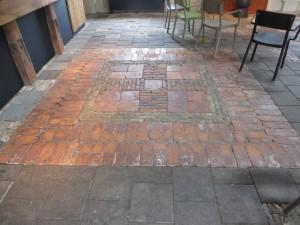 Verlaagde vloer in de zaal, met hergebruik van oude tegels en klinkers.