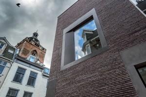 Bij de hoek in de Massegast is een etalageraam als extra accent een verdieping hoger geplaatst. Het metselwerk is uitgevoerd in de Kolumba van de Deense steenfabriek Petersen Tegl.