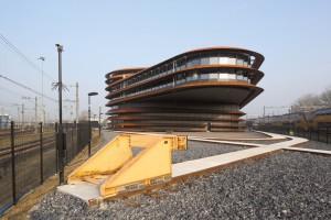 Het gebouw ligt op een terp tussen twee drukke spoorlijnen in Utrecht en heeft op de hoek een spectaculair overstek van 23 meter.