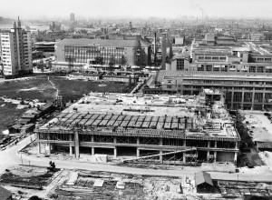 Op voorgrond het gebouw van Vroom & Dreesmann in aanbouw