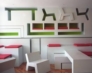 Martinez-Gallery-NY. In de clubruimte kunnen bezoekers stoelen, tafels, banken en kussens uit de wand halen en ze weer terugplaatsen wanneer de vloer leeg moet zijn voor een feestje