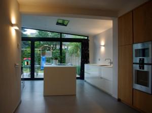 De nieuwe uitbouw met eetkeuken in de tuin achter een bestaande woning in Eindhoven door MWarchitectuur. Door het dak op te tillen komt er meer daglicht binnen • Foto's MWarchitectuur.
