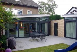 De twee uitbouwen met links de nieuwe eetkeuken en rechts de speelkamer. Ondanks de uitbouwen is er nog genoeg van de tuin over.