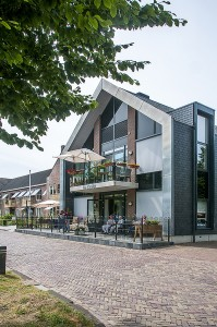 De uitbouw aan de straat met balkon op de verdieping en groot terras op de begane grond • Foto's Grunstra Architecten.