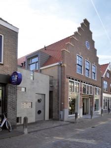 Benschopperstraat 16 met trapgevel, links de entree naar woningen. Boven de winkelpui komt nog een zinken lijst. Rechts is een deel van Benschopperstraat 14 zichtbaar.