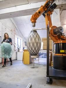 Met een robotarm worden carbondraden om een contramal gespannen in een complexe wiskundige figuratie. Atelier Robotiq.