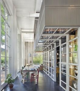 Doorzicht met links deuren naar de tuin en in het midden de 'tafel van het huis' waarin alle toegepaste sloopmaterialen zijn verwerkt. Foto Jeroen Musch.
