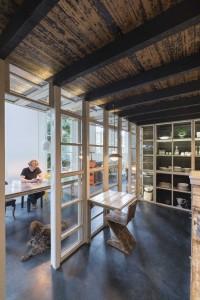 Rolf aan de 'tafel van het huis' vanuit de keuken gezien, ook de beroemde Z-stoel van Gerrit Rietveld is nagemaakt uit sloopmateriaal
