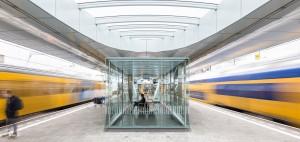 Symmetrisch beeld van rijdende treinen op het perron van het vernieuwde station Arnhem, ontworpen door Ben van Berkel