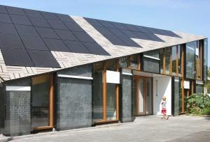 De Trombewand in de entreegevel op het zuidoosten. Voor een goede oriëntatie van de dakhelling met zonnecellen op het zuiden is de nok van het dak diagonaal over het gebouw gelegd.