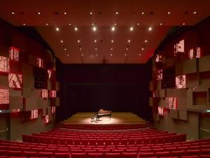 Grote zaal met akoestische dozen tegen de zijwanden, waarvan een deel licht geeft, dat in intensiteit en kleur geprogrammeerd kan worden, passend bij sfeer van de voorstelling.