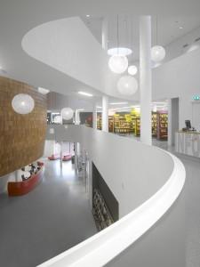 Foyer op de eerste verdieping met vide en bibliotheek. Op de gestuukte balustrades voorkomt een opzetrandje dat er glazen naar beneden vallen.