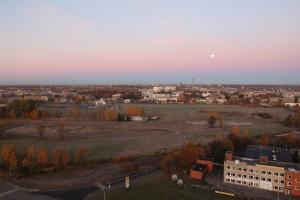 het te ontwikkelen gebied in Riga, gezien naar het westen. Links staat nog een oud gebouw van het goederenspoor, omgeven door parkeerterreinen.