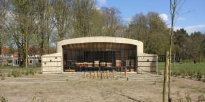 De geopende zuidgevel levert naast een publieke contactplaats voor de parkbezoekers ook direct invallend zonlicht op de bijenkasten. Op de voorgrond de zonnewijzer en de zonnewende