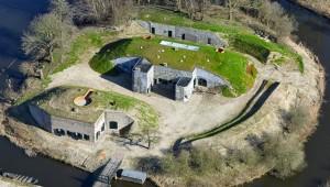 Links het kruithuis met uitzichtpunt op het dak, in het midden het schiethuis en remises, daarachter de kazemat.  Foto Nieuwe Hollandse Waterlinie