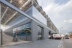 Vuilnisauto's rijden het nieuwe bedrijfsgebouw van de Stadsdeelwerf Amsterdam-Zuid binnen