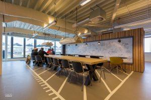 Mannen kaarten in de kantine van het nieuwe bedrijfsgebouw van de Stadsdeelwerf Amsterdam-Zuid met op de achtergrond een tekening van Jan Rothuizen
