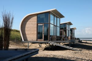 Slaapstrandhuisjes Groede. Ontwerp van WTS architecten. Geïnspireerd op een schelpvorm, en op die oude rieten strandstoelen. Een huisje dat zowel beschutting als uitzicht biedt. Huurders vinden in het huisje een iPad waarop ze real time kunnen zien welke schepen er voorbij varen