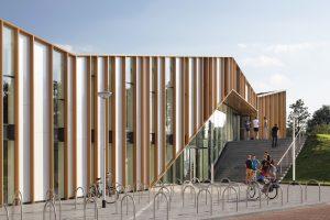 De gevel van multifunctioneel centrum Het Anker in Zwolle is voorzien van verticale aluminium lamellen, opgevuld met glas en plaatmateriaal.