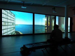 De 20 meter brede projectiewand geeft een intrigerend beeld van de vijf gebouwen die centraal staan in de expositie.