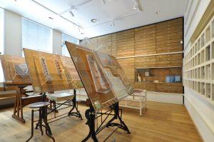 Themazaal architectenatelier, met tekentafels en tekeningenladenkast.
