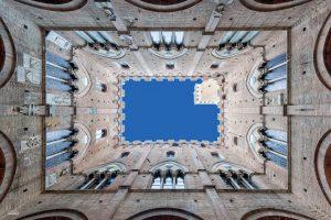 De camera omhoog richten leidt tot een abstract beeld van de Torre del Mangia in Siena