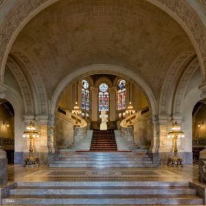 Trappen en loper leiden de kijker naar het beeld in het midden van de symmetrische compositie in het Vredespaleis in Den Haag