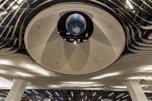 Plafond Luxury World. De verlichtingsarmaturen zijn niet gekocht, Schiphol neemt voor tien jaar een vaste hoeveelheid 'lumen' af van leverancier Philips, die eigenaar blijft van de lampen. Dat betekent dat Philips ook verantwoordelijk is voor onderhoud en eventueel vervanging
