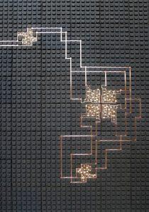 Terra ducit. Ruwe aarde gebruikt als drager voor een geleidende koperlaag die zich systematisch door het landschap slingert, zo steden van licht met elkaar verbindend. Als losse lichttegel of als wandbekleding per vierkante meter • Foto: Kranen/Gille