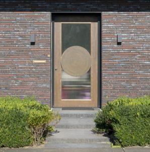 De voordeur in tombak (koper-zink legering) in een strak donkergrijs metalen kader.