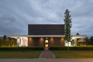 Vanaf de Museumlaan oogt het huis als een bakstenen kubus met aan weerszijden glazen erkers onder een slank overstek.