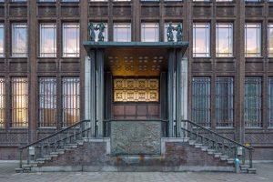 Hoofdentree met bronzen deuren, omlijst door Frans kalksteen. De entree is uitgerust met een verhoogd trapbordes, natuurstenen treden en bronzen leuningen. Aan de voorzijde van het bordes is een bronzen embleem van de Nederlandse Handelsmaatschappij, ontworpen door N. Klaassen, aangebracht.