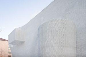 Kukje Gallery in Seoul, een betonnen gebouw overspannen met een constructie van geschakelde ringen, een soort maliënkolder