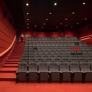 Interieur filmzaal met achterin steil oplopende tribune.