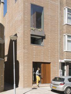 6. Voorgevel met brede deurpartij en hoog venster over twee verdiepingen.