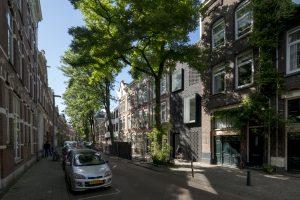 De Schoonoordstraat met rechts skinnySCAR, met een moderne gevel in donkere baksteen. Twee grote vensters steken uit de gevel, drie vensters zijn verscholen achter halfopen metselwerk • Foto Ossip van Duivenbode.