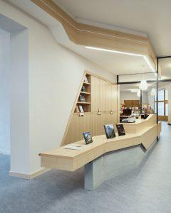 De nieuwe balie voor de ansichtkaartverkoop loopt door in de balie van de boekhandel, die met vouwdeuren kan worden afgesloten. Boven de balies zijn nieuwe akoestische plafonds met een lichtlijn afgezet. Foto Archimage Meike Hansen
