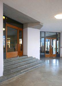 Links de nieuwe deur naar het trappenhuis, die voorheen achter een wand verborgen was. Rechts hergebruikt entreeportaal. De schuine deuren van het portaal zijn verplaatst en gespiegeld, zodat het portaal ruimer is en de routing logischer. Foto Pieter van der Ree.