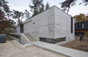 Vanaf de straat loopt een betonnen loper naar de dubbele trap, die leidt naar de woning boven en het kantoor beneden. De betonnen binnen- en buitenschil zijn ter plaatse gestort. Plaatnaden en conusgaten zijn nauwkeurig bepaald. Foto Jan Willem Schouten.