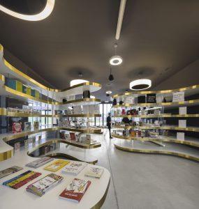 In de museumwinkel is het meubilair ontworpen door Nio in vloeiende vormen. Perspex kokers dragen de met goudkleurig band afgebiesde witte composiet panelen. Foto Fernando Guerra