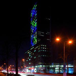 Westpoint, Tilburg. Gekleurde vlakken op betonstroken in de gevel van de hoogste woontoren van de stad zorgen bij daglicht voor een bijzonder beeld. In het donker verandert dat beeld weer doordat er licht op die gekleurde vlakken wordt geprojecteerd • Foto's Norbert van Onna