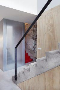Uitgesproken kleuren als een verkeersrode trap, brengen sfeer in het neutrale interieur.