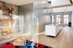 Het hart van beide woningen is een keukeneiland. Bovenop de kast van gegalvaniseerd metaalplaat verbindt een gaanderij beide slaapkamers.