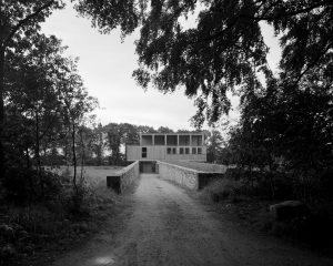 Uit het coulisselandschap rijzen twee 70 meter lange stenen muren op langs de oprijlaan. Op het Bentheimer stenen onderstel ligt een houten doos met enorme ramen.