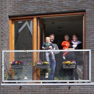 Corné van de Kraats met vrouw en zonen op het balkon aan de straat. Foto Jacqueline Knudsen.