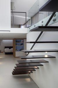 De trap is gemaakt van massief stalen delen. De kast met blauwe achterwand herbergt een uittrekbare schuifwand die de logeerkamer afsluit
