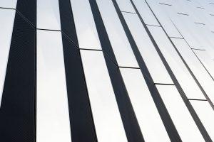 verdiepingshoge stalen en aluminium sandwichpanelen van 6m x 1,2 m x 200 mm. De aluminium platen zijn ca 30 cm naar buiten gevouwen. De vouw loopt schuin, waardoor de lichte stroken van onder naar boven toe steeds breder worden. Door de strepen te verjongen, oogt het gebouw slanker