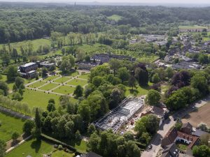 Het paviljoen in aanbouw tussen de historische gebouwen op het landgoed. Oostwegel wil op het zandveld aan de overzijde van de weg een wijngaard aanleggen.. Foto Air Vision.