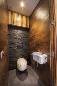 De wanden in het toilet zijn bekleed met natuursteen en roestkleurige, keramische tegels