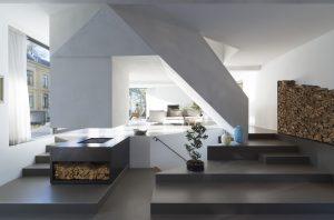 Doorzicht vanuit de eetkeuken naar de zitkamer. De trappen naar souterrain en verdieping steken schuin in de kamer • Foto Jeroen Musch